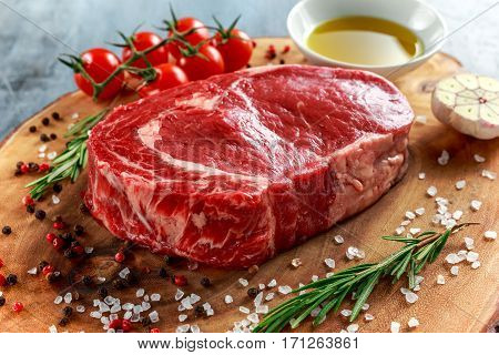 Fresh Raw Beef Steak Ribeye, with salt, peppercorns, rosemary, tomatoes and olive oil.
