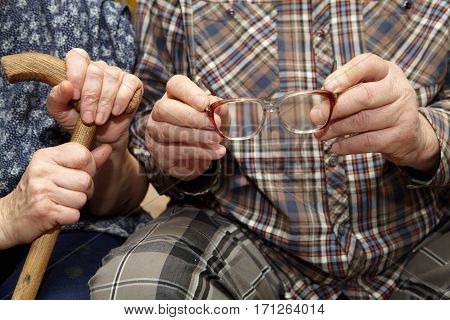 Old Couple. Hands With Eyeglasses