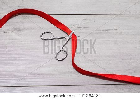 Miniature iron scissors in the process of cutting the red ribbon on the wooden gray background. Concept. Tailor table. Scarlet ribbon lies on a wooden surface