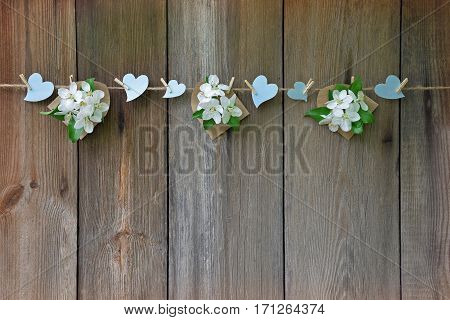 A beautiful ornament of blooming apple trees and blue hearts handmade. Declaration of love. Rustic style. Celebratory background. Wedding. Valentine's Day. Mothers Day. Wooden plank old background.