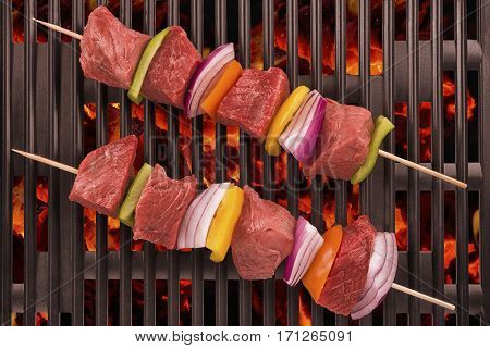 Close up of red meat skewers being grilled in a barbecue.