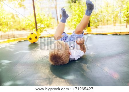 Happy teenager boy plays outdoors in garden jumping high in the sky on trampoline