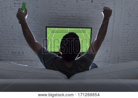 couch back view with young man home alone watching Grand slam tennis match in television enjoying and celebrating victory holding drinking beer bottle gesturing on sofa happy excited