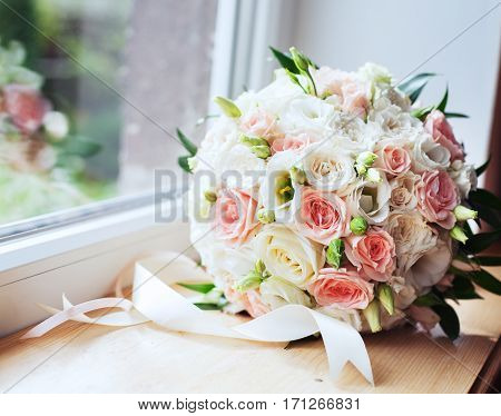 Beautiful bouquet on a window sill. The concept of marriage and love.