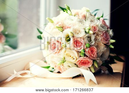 Beautiful wedding bouquet on the windowsill. The concept of marriage and love.