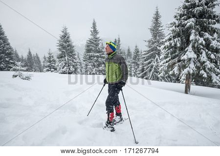Man In Snowshoes Enjoying Life While Traveling In The Winter Mountains