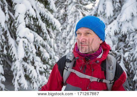 Portrait of dreaming traveler who enjoying a wonderful adventure in the winter mountains.