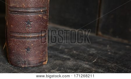Antique leather bound book standing alone on an old wooden bookshelf