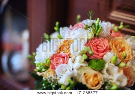 Colorful wedding bouquet and rings. The concept of marriage and love.