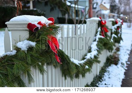Snow covered evergreen garland draped along a white picket fence