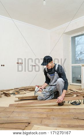Installing a wooden floor. The worker fixes the board using a nail gun.