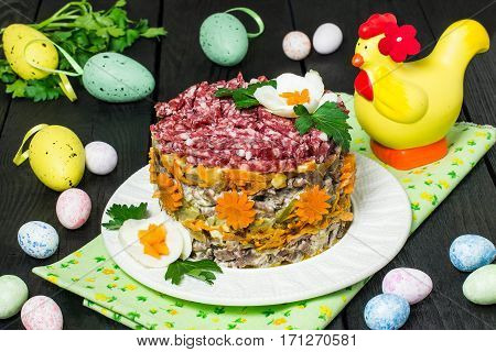 Multilayer festive salad with beef pickled cucumbers and carrots on a dark wooden background with eggs and bunny. Easter food Easter recipe. Selective focus