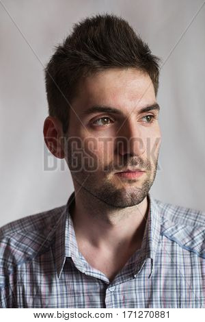 frontal portrait of a young man in a plaid shirt over a white background stylish man express emotions