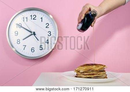 Pancakes with maple syrup on a pink background with a clock