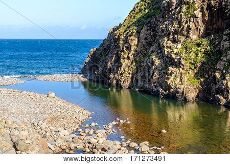 Coast near Sao Jorge Madeira Island. The mountain river flows into the ocean.