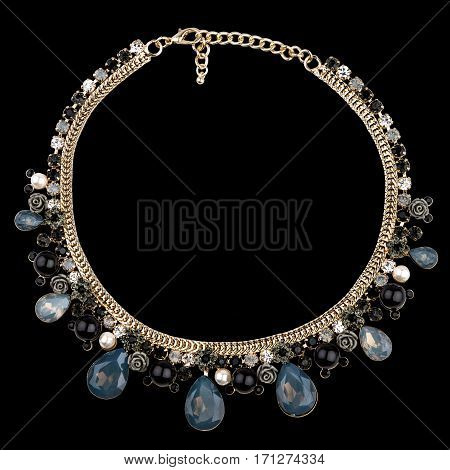 Golden necklace with sapphire on black background