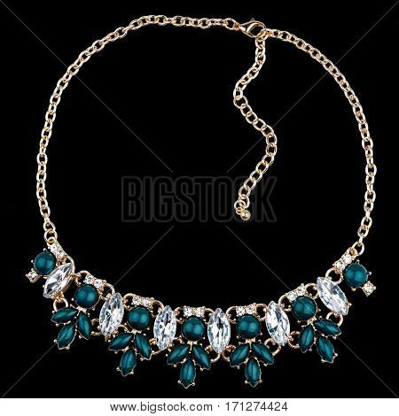 Golden necklace with diamonds on black background