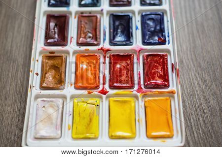 High water watercolor paints on the wooden background. Tools for drawing students artists. Watercolor close up. Used paint. A set of warm and cool colors. Vintage texture. Solid watercolor in tiles. Bright hues. Tool to perform drawing work