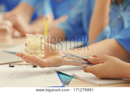 Student holding dental jaw model and tools, closeup