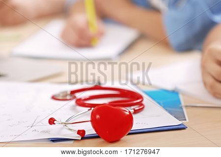 Stethoscope, miniature heart and clipboard on desk and interns on background, closeup