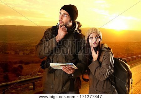 Young couple with map on beautiful landscape background