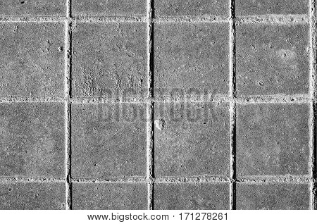 Concrete or cobble gray pavement slabs or stones for floor. Traditional backyard or road paving. Black and white pavement slabs rattern