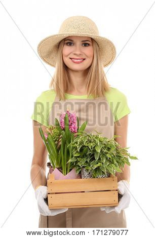 Beautiful female florist holding wooden box with house plants on white background