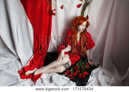 Red-haired girl with blue eyes and pale skin in a red coat. Woman with flowers. Curling hair. Gothic style on a white background.