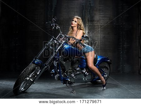 Sexy woman on a motorcycle in the room