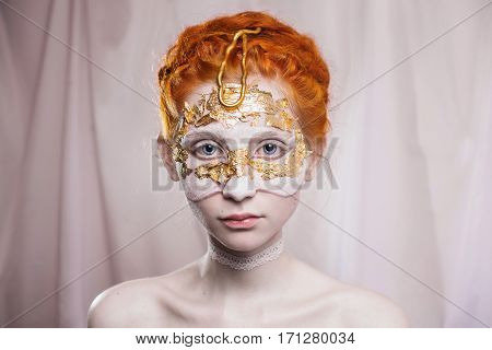 High wedding hairstyle in the Greek style. Vogue style portrait of a girl with a red white and golden bodyart on her face. Body painting project. Woman painted white and gold colors. Insight concept. Makeup