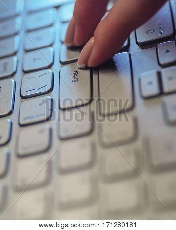 Woman fingers on the laptop keyboard in office