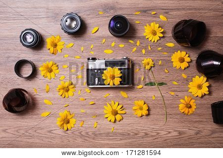 Old vintage camera on wooden background. Manual focus lenses and film are on the table with yellow flowers and petals. Flat lying.