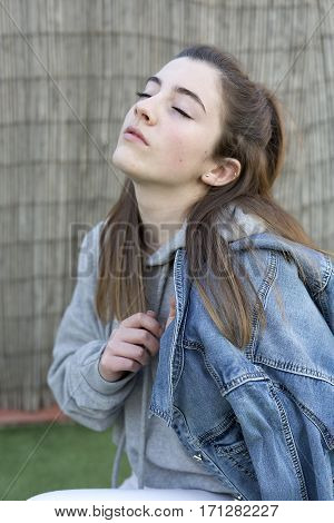 Young Woman With A Denim Jacket Over Her Shoulder And Eyes Closed.