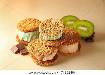 Delicious ice cream cookie sandwiches with kiwi and chocolate on beige background