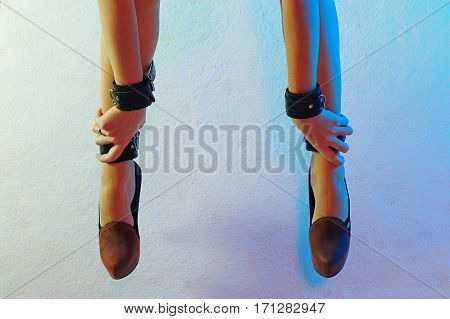 Sexy long female legs in high heel shoes and leather cuffs chained together with hands in leather cuffs against colorful texturized background horizontal view