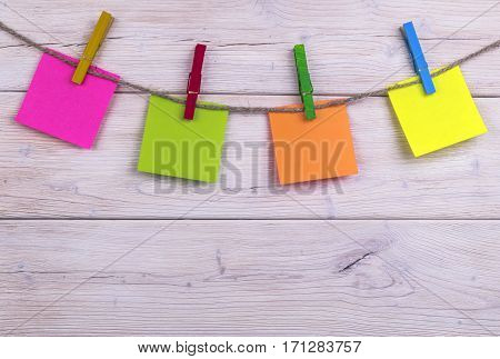 Clothespin hanging with blank photo papers on white wooden background texture