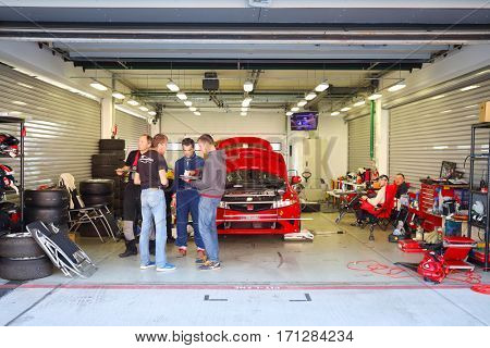 MOSCOW - SEP 3, 2016: People and red car in garage during Race of Stars At wheel Magazine with participation of best Russian riders at Moscow Raceway