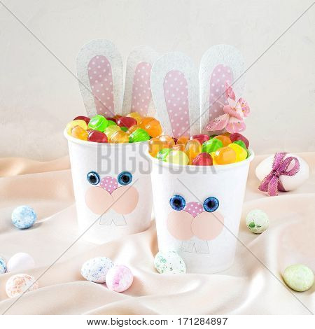 Paper cups in the form of funny Easter Bunny with candy. Homemade applique on paper cups. The idea for children gifts. DIY concept for the celebration of Easter. Square image