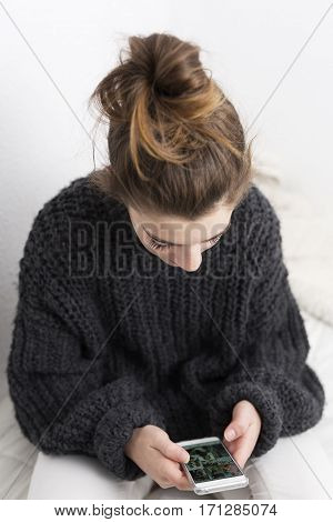 Young Woman Looking At The Mobile Phone On A White Background.