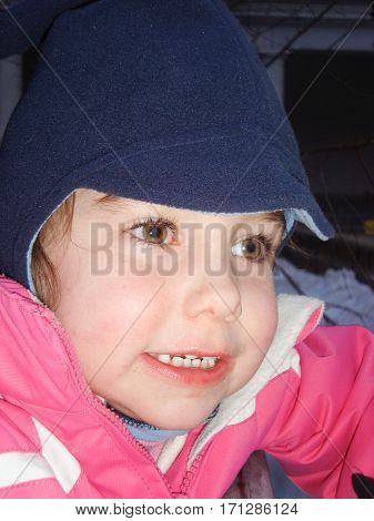 Girl Child With A Blue Hat And A Big Pink Jacket For The Cold Winters