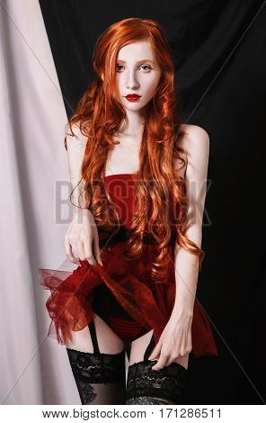 The red-haired doll girl with long curly hair posing in sexy scarlet lingerie on black and white background. Young red-haired woman in stockings garter posing as a model.
