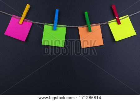 Clothespin hanging with blank photo papers on black background texture