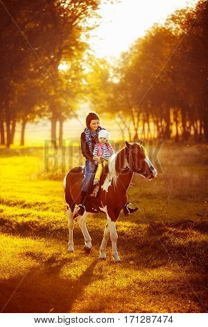 Little girl and her mother riding a horseback in the sunny meadow. Outdoors shot.