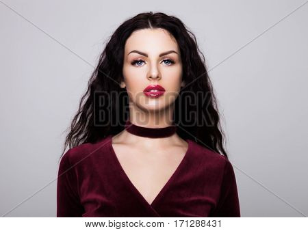 Sexy beautiful fashion model wearing velvet luxury dress with curly hair and red lips on grey background