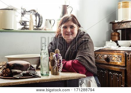 TELFORD UK - CIRCA 2013: A woman poses in Victorian dress in the squatters cottage at Blists Hill Museum Ironbridge UK