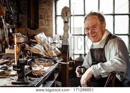 TELFORD UK - CIRCA 2013: Leather worker at Blists Hill Victorian Museum Ironbridge UK