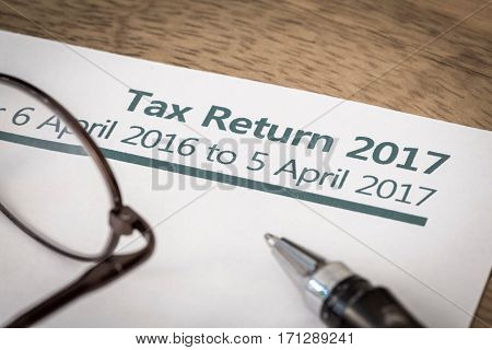 UK Income tax return form for 2017 on a desk with pen and glasses