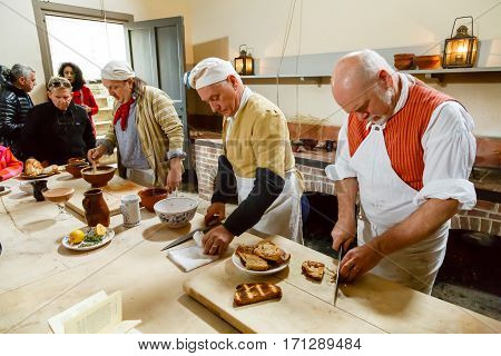 LONDON - CIRCA 2014: Chefs in traditional costume cooking in the Royal Kitchens Kew Gardens London UK