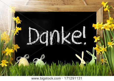 Blackboard With German Text Danke Means Thank You. Sunny Spring Flowers Nacissus Or Daffodil With Grass, Easter Egg And Bunny. Rustic Aged Wooden Background.