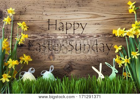 Wooden Background With English Text Happy Easter Sunday. Easter Decoration Like Easter Eggs And Easter Bunny. Yellow Spring Flower Narcisssus With Gras. Card For Seasons Greetings